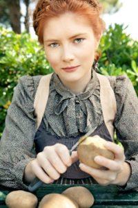 Jeune femme, éplucher les pommes de terre