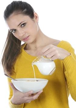 Jeune femme, verser, lait, dans, a, bol